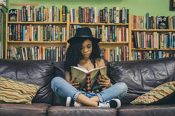 Girl sitting cross-legged reading a book in front of a filled bookshelf