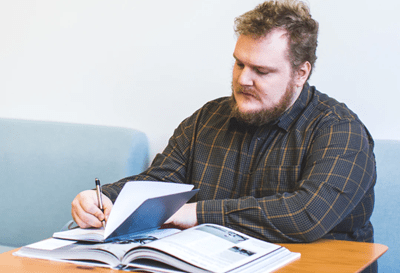 man studying with pen and notebook